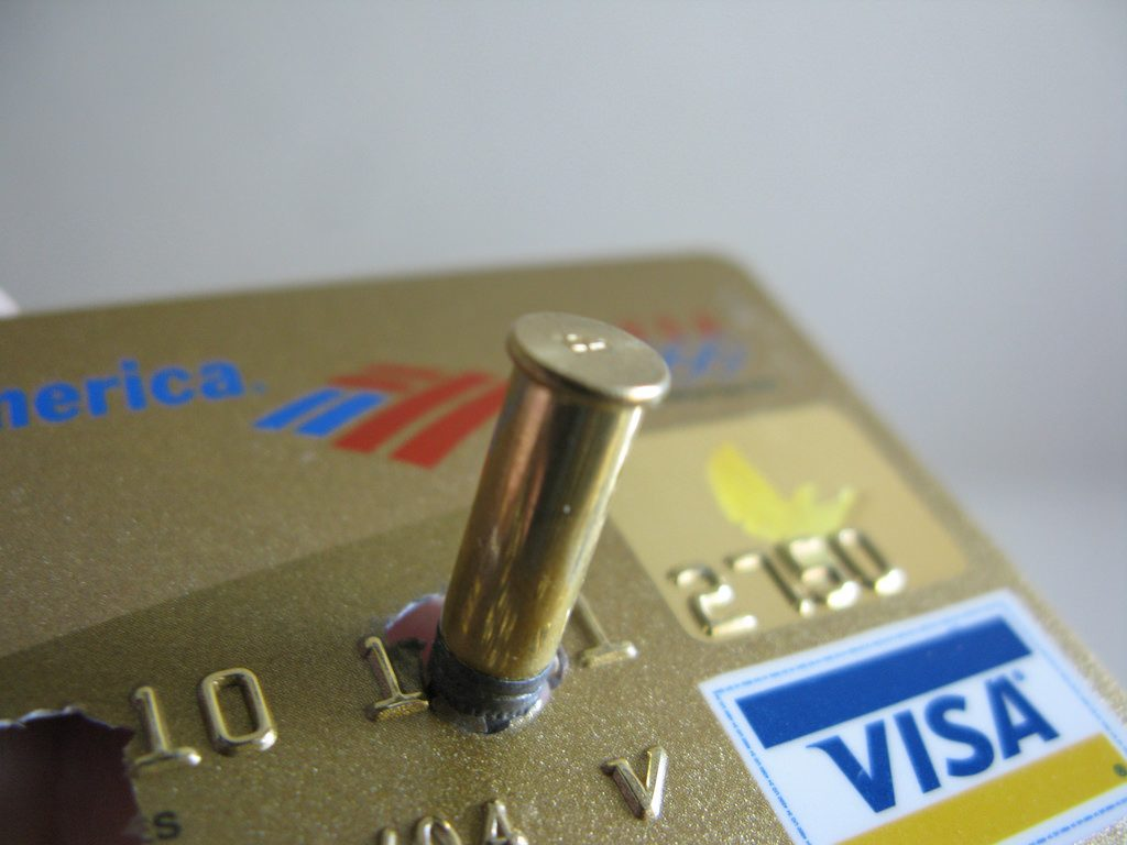 A Bullet including the shell casing stuck into a gold credit card