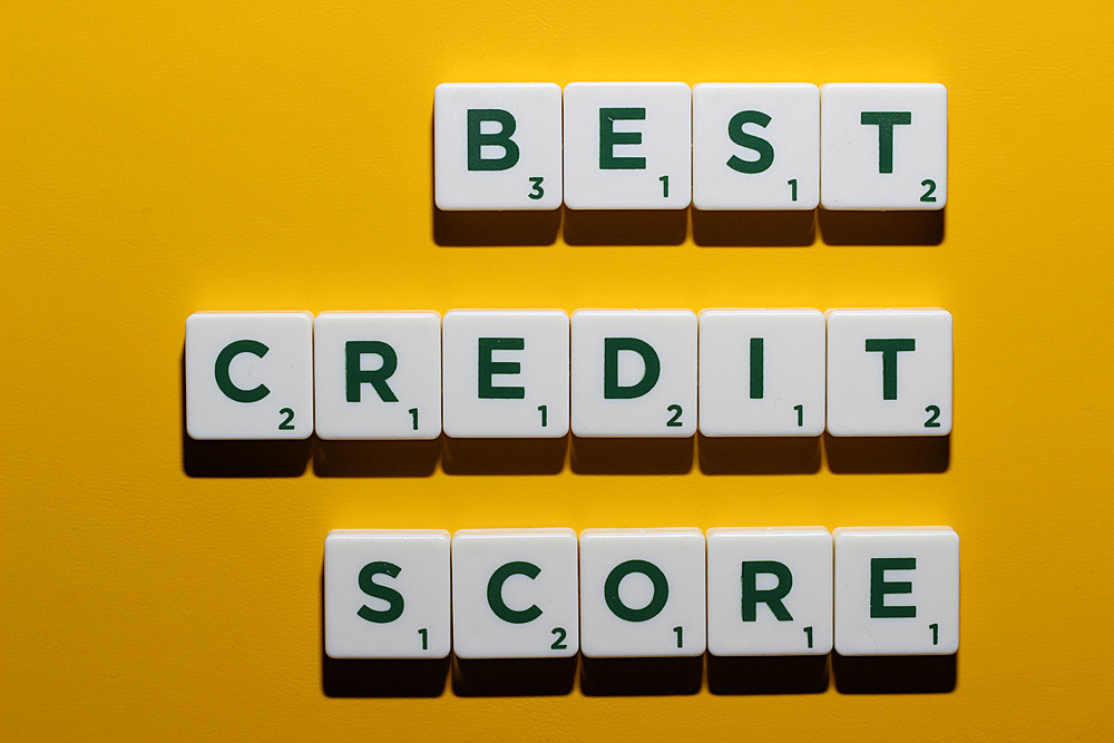 Best credit score in green letters spelled out on white scrabble blocks on a yellow background
