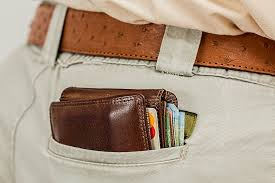Brown wallet protruding from a mans back pocket