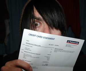 Man with long black hair looking in shock at his credit card statement